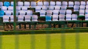 De lege blauwe en witte zetels in een voetbal of voetbalgebied en het plastiek van het stadiongras zit open voor royalty-vrije stock afbeelding