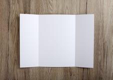 De lege brochure van poortvouwen op houten achtergrond om uw DE te vervangen stock afbeelding