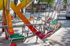 De lege carrousel van de kindzetel op kettingen in de zomerdag stock afbeelding