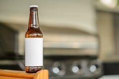 De lege Fles van het Etiketbier op lijst dichtbij Grill Royalty-vrije Stock Afbeelding