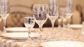 De lege geplaatste glazen, vork, mes dienden voor diner in restaurant met comfortabel binnenland stock videobeelden