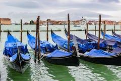 De lege gondels dokten tussen houten die meertrospolen in geteerd zeildoek in regenachtig November-seizoen in Venetië, Italië wor stock afbeeldingen