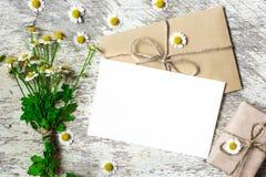 De lege groetkaart en de envelop met witte kamille bloeien en uitstekende giftdoos Stock Afbeeldingen