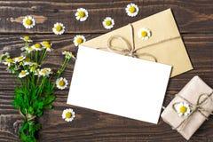 De lege groetkaart en de envelop met witte kamille bloeien en uitstekende giftdoos Royalty-vrije Stock Fotografie