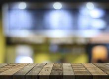 De lege houten lijstvloer voor heden en toont producten op koffiewinkel en de achtergrond van de nachtclub royalty-vrije stock fotografie