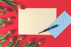 De lege kaart, de pen, de blauwe envelop en de de rode lentetulpen bloeien op rode achtergrond stock afbeeldingen