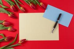 De lege kaart, de pen, de blauwe envelop en de de rode lentetulpen bloeien op rode achtergrond stock afbeelding