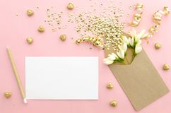 De lege kaart met envelop, schittert lovertjes, confettien, harten en bloemen op een zacht roze backgroundgold Spot omhoog stock afbeeldingen