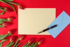 De lege kaart, de pen, de blauwe envelop en de de rode lentetulpen bloeien op rode achtergrond royalty-vrije stock fotografie