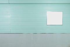 De lege omlijsting hangt op pastelkleur munt-blauwe houten muur, en glanzende grijze textiel Royalty-vrije Stock Afbeelding