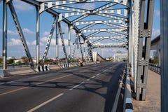 De lege oude brug van de staalstructuur over de rivier op achtergrond van de wolken de blauwe hemel stock foto's