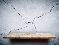 De lege plank van de Rotsvertoning op gebarsten muur Stock Foto