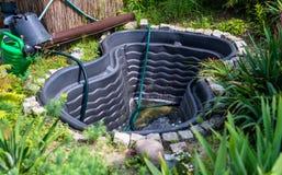 De lege, plastic tank van het tuinwater groef in de gronden op de achtergrond van installaties, zichtbare gieter en een emmer royalty-vrije stock fotografie