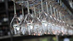 De lege schone glazen hangen voor dranken op de bar in het restaurant stock video