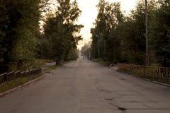 De lege straat bij nacht met landelijke slechte asfaltweg stock afbeeldingen