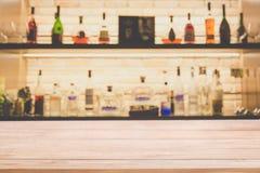 De lege teller van de pijnboom houten bar met onduidelijk beeld achtergrondflessen Re stock afbeeldingen