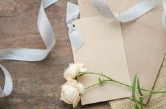 De lege uitnodigingskaart met bruine envelop en nam bloemen op wo toe Stock Foto's