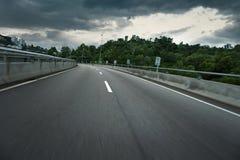 De lege weg van het stadsasfalt met donker donderwolken en motieonduidelijk beeld Stock Fotografie