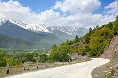 De lege wegkronkelweg in de bergen, blauwe skywith betrekt, bergpieken op de sneeuw en de groene heuvelsachtergrond stock foto's