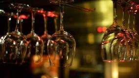 De lege wijnglazen hangen boven een barrek stock video
