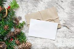 De lege witte kaart van de Kerstmisgroet en de envelop met spar vertakken zich, voedseldecoratie en denneappels Stock Fotografie