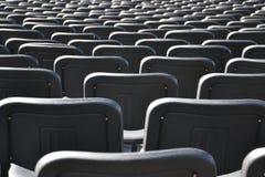 De lege zwarte plastic stoelen alligned in vele rijen Stock Foto's