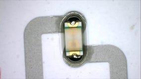 De LEIDENE component zet op zilveren kring op door terugvloeiings te solderen De macro van zilveren zelfklevende inkt die en prod stock video