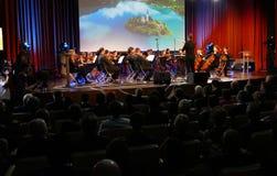 De leider die symfonieorkest met uitvoerders op achtergrond leiden tijdens de openingsceremonie van Zaken tapte Strategisch Forum royalty-vrije stock afbeeldingen