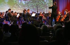 De leider die symfonieorkest met uitvoerders op achtergrond leiden tijdens de openingsceremonie van Zaken tapte Strategisch Forum stock afbeeldingen