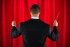 De leider die van het orkest met zijn knuppel leidt Stock Foto's