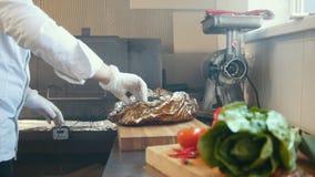 De leider op keuken van restaurant treft van een brok van gerookt vlees op een houten raad voorbereidingen stock video