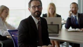De leider van commercieel team controleert zijn mobiel en glimlacht aan camera stock footage