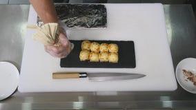De leider zet sushi op de raad Stock Fotografie