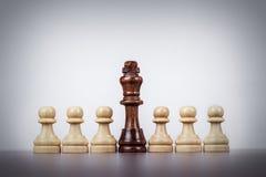 De leidingsconcept van de schaakkoning over grijze achtergrond Stock Foto's