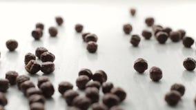 De lengte van bruine ronde cacaocacao schilfert het vallen op witte houten lijst met zachte nadruk af stock video
