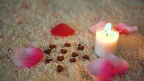 De lengte van decoratie nam bloemblaadjes en kaars het branden op zand toe De dag van de valentijnskaart stock videobeelden