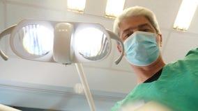 De lengte van een mannelijke tandarts die met de patiënt spreken en zijn tanden controleren, de tandarts stelt vragen en de gedul stock videobeelden