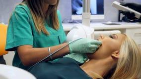 De lengte van een vrouwelijke geduldige zitting in de tandartsen zit voor en die een vrouwelijke tandarts neemt een röntgenstraal stock videobeelden