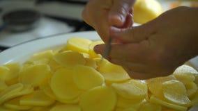 De lengtevrouw snijdt aardappels 4K stock footage