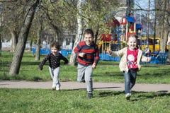 De lente begaayut kinderen op het gras dichtbij de speelplaats Stock Afbeeldingen
