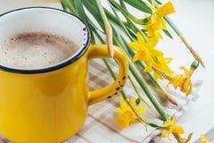 De lente bloeit gele narcissen met een kop van koffie, dichte cappuccino, royalty-vrije stock fotografie
