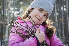 In de lente in de bostribunes een klein meisje met een boeket van wilg royalty-vrije stock afbeeldingen