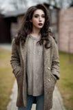 De lente in de stijl van het land Volledig lengteportret van jonge vrouw in witte gebreide sweater en bonthoed die zich in de voo Royalty-vrije Stock Foto's