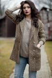 De lente in de stijl van het land Volledig lengteportret van jonge vrouw in witte gebreide sweater en bonthoed die zich in de voo Stock Foto