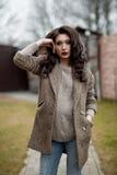 De lente in de stijl van het land Volledig lengteportret van jonge vrouw in witte gebreide sweater en bonthoed die zich in de voo Stock Afbeeldingen
