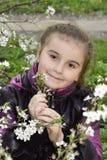 De lente in de tuin een klein meisje die een kersentak houden. Royalty-vrije Stock Afbeeldingen