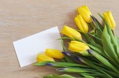 De lente gele tulpen en Witboek die op hout liggen Stock Afbeeldingen