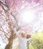 De lente jong meisje die vóór kersenboom springen stock foto