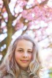 De lente jong meisje vóór kersenboom stock afbeeldingen