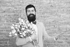 De lente overal de dag van vrouwen Bloem voor 8 Maart De lentegift De gebaarde bloemen van de mensen hipster liefde Gebaarde mens stock foto's